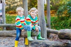 Two little kid boys having fun on autumn playground Stock Photo