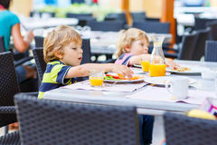 Two little kid boys having healthy breakfast in hotel restaurant Royalty Free Stock Photo