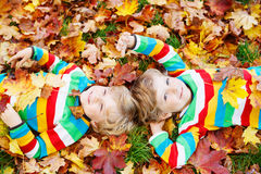 Two little kid boys laying in autumn leaves in colorful clothing Stock Images