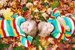 Two little kid boys laying in autumn leaves in colorful clothing Stock Image