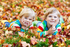 Two little kid boys laying in autumn leaves in colorful clothing Royalty Free Stock Image