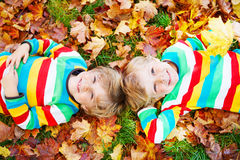 Two little kid boys laying in autumn leaves in colorful clothing Royalty Free Stock Photos