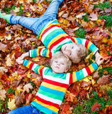 Two little kid boys laying in autumn leaves in colorful clothing Stock Photography