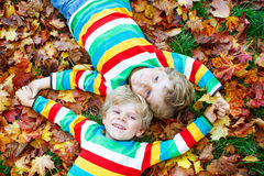 Two little kid boys laying in autumn leaves in colorful clothing Stock Photo