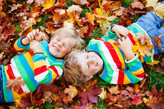 Two little kid boys laying in autumn leaves in colorful clothing Stock Photos