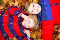 Two little kid boys lying in autumn leaves in colorful fashion fall clothing. Happy healthy siblings having fun in stock photos