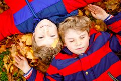 Two little kid boys lying in autumn leaves in colorful fashion fall clothing. Happy healthy siblings having fun in stock images