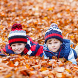 Two little kid boys lying in autumn leaves, in park. Stock Photos