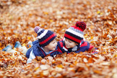 Two little kid boys lying in autumn leaves, in Royalty Free Stock Photo