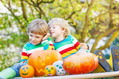 Two little kid boys making jack-o-lantern for halloween in autum. N garden, outdoors. Happy children having fun together with traditional party Stock Photography