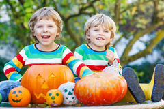 Two little kid boys making jack-o-lantern for halloween in autum. Two little kid brother boys making jack-o-lantern for halloween in autumn garden, outdoors Stock Photography