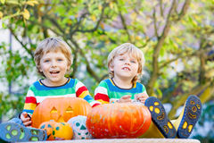 Two little kid boys making jack-o-lantern for halloween in autum. Two little kid brother boys making jack-o-lantern for halloween in autumn garden, outdoors Stock Photos