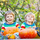 Two little kid boys making jack-o-lantern for halloween in autum. Two little kid brother boys making jack-o-lantern for halloween in autumn garden, outdoors Stock Images