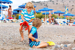 Two little kid boys playing on beach with stones Royalty Free Stock Image