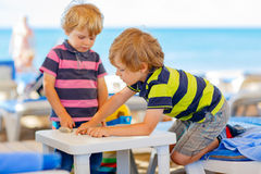 Two little kid boys playing on beach with stones Stock Photos