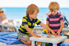 Two little kid boys playing on beach with stones Stock Image