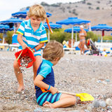 Two little kid boys playing on beach with stones Stock Photo
