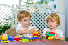 Two little kid boys playing with plastic blocks together Royalty Free Stock Photo