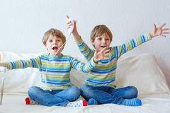 Two little kid boys playing video game at home Stock Image