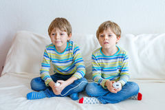 Two little kid boys playing video game at home Royalty Free Stock Photo