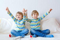Two little kid boys playing video game at home Stock Photos