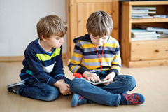 Two little kid boys reading a book at home. Older schoolboy reading for his brother, preschool sibling a fairytale or story. Family, children, education and Stock Image