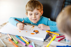Two little kid boys at school painting a story with colorful pens Royalty Free Stock Photo