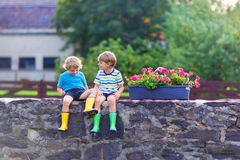 Two little kid boys sitting together on stone bridge Stock Photos