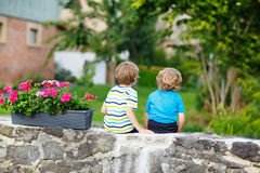 Two little kid boys sitting together on stone bridge Royalty Free Stock Images