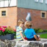 Two little kid boys sitting together on stone bridge Royalty Free Stock Photo