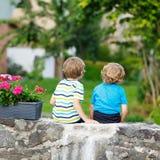 Two little kid boys sitting together on stone bridge Royalty Free Stock Image