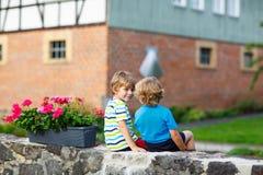 Two little kid boys sitting together on stone bridge Stock Photo