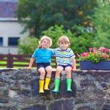 Two little kid boys sitting together on stone bridge Stock Image