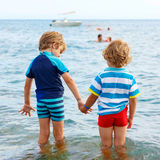 Two little kid boys taking bath in ocean. Two little blond kids boys having fun by taking bath in ocean or sea. Funny siblings, children holding hands. Vacations Stock Images