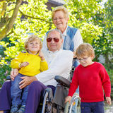 Two little kid boys, their grandmother and grandfather in wheelc Royalty Free Stock Photo