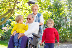 Two little kid boys, their grandmother and grandfather in wheelc Stock Image