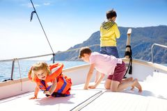 Two little kid boys and toddler girl enjoying sailing boat trip. Family vacations on ocean or sea on sunny day. Children royalty free stock photos