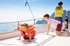 Two little kid boys and toddler girl enjoying sailing boat trip. Family vacations on ocean or sea on sunny day. Children stock image
