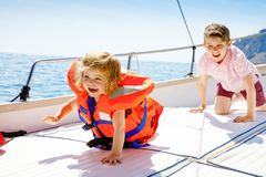 Two little kid boys and toddler girl enjoying sailing boat trip. Family vacations on ocean or sea on sunny day. Children stock photos