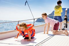 Two little kid boys and toddler girl enjoying sailing boat trip. Family vacations on ocean or sea on sunny day. Children stock photography