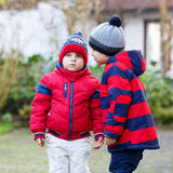 Two little kid boys walking together outdoors. Two little kids, friends holding hands. Adorable boys in bright red clothes. Happy children outdoors, spring Stock Images