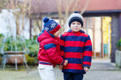 Two little kid boys walking together outdoors. Two little kids boys, friends holding hands and hugging. Adorable siblings in bright colorful clothes. Happy Royalty Free Stock Images