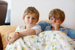 Two little kid boys watching tv at home Stock Photo
