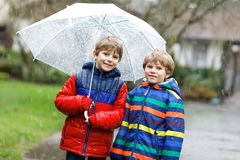 Two little kid boys on way to school walking during sleet, rain and snow with an umbrella on cold day Stock Image