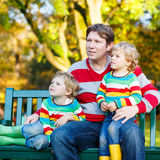 Two little kid boys and young father sitting together, autumn, o Royalty Free Stock Photos