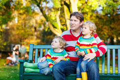 Two little kid boys and young father sitting together, autumn, o Stock Photo