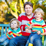 Two little kid boys and young father sitting together, autumn, o Royalty Free Stock Photo