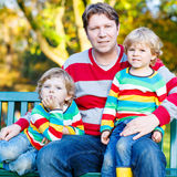 Two little kid boys and young father sitting together, autumn, o Stock Photos