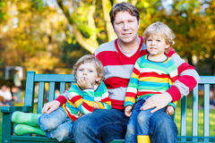 Two little kid boys and young father sitting together, autumn, o Stock Photography