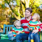 Two little kid boys and young father sitting together, autumn, o Stock Image